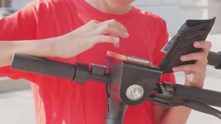 yakın : Young person using credit card and smartphone for contactless payment of electric kick scooter rent. Customer completing transaction with NFC technology. Mobile app to  shared rental vehicle service Stok Video