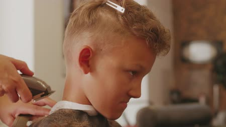 aparar : Barber shingling smiling teenager boy, style haircut in barbershop, working by clipper. Hairdresser hands using hair trimmer for man head-dress. Hairstyle on shot hair. Preparing boy for celebration Stock Footage