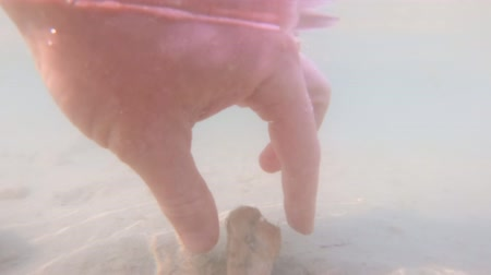 muddy : Hand taking stone from river bed underwater, foot stepping on sand in cloudy water, air bubbles, sand stirring up, handheld shot. Steps in muddy water, dirty cloud of floating mud underwater, shallow Stock Footage