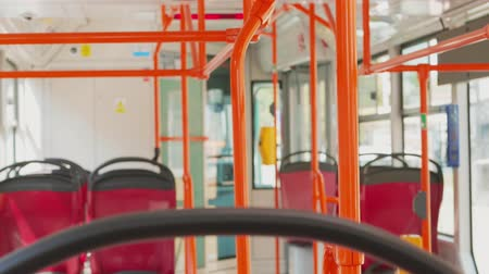 inside bus : Empty moving modern city tram, rails and seats. Public transport on day street, handheld shot. Bus interior, places for passengers, no people inside, focus on handrails. Municipal transportation Stock Footage