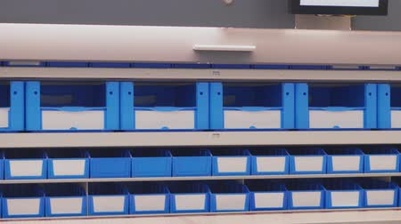 Automated vertical carousel for storing components in storage warehouse. Blue and white boxes for production parts moving top and down. Storing of documents in automatic shelves. Automation technology