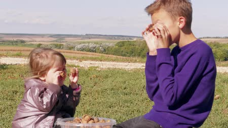 понимание : Happy children covering eyes with walnuts from full plastic bucket at family farm. Boy and little girl having fun with nuts instead of eyeballs. Kids holding fruits at eyes at autumn outside. Harvest