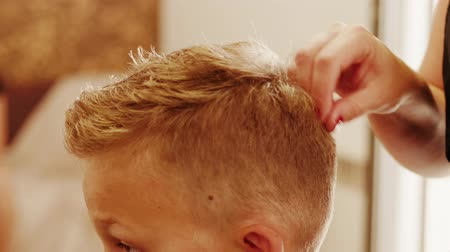 Barber hands styling boy blond hair after cutting for man head-dress in hairdressing beauty saloon. Hairdresser setting teenager hair on head making style haircut by fingers in barbershop. Fixing hair