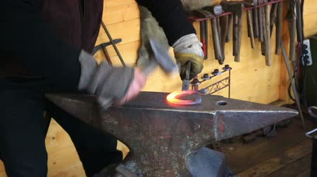 zanaat : smith forges a horseshoe on an anvil in a smithy Stok Video