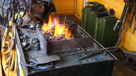 open hearth : View at forge shop with burning flame and tools near