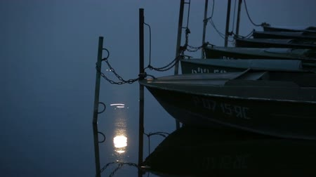 barco : Parked boats and moon reflecting in water at berth