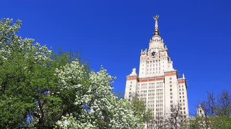 rusya : Spring gardens near the main building of MSU Moscow State University under clear blue sky. Stok Video