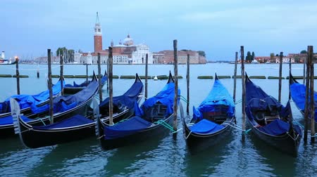 Gondolas moored by Saint Mark square with San Giorgio di Maggiore church in the background during twilight blue hour, Venice, Italia