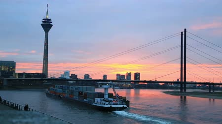 The cargo ship for transportation of containers floats down the river Rein a sunset Vídeos