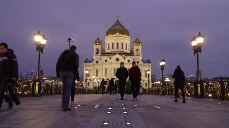 People walk along the Patriarchal bridge in the evening, in the background Christ the Savior Cathedral, timelapse 4K
