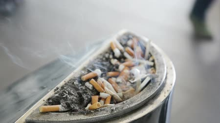 Smoldering cigarette butts in a large metal ashtray, full of ashes.