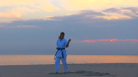 истребитель : young woman training karate on sunset beach Стоковые видеозаписи