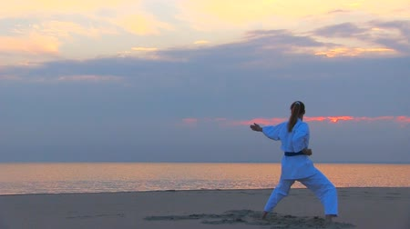 ремень : young woman training karate on sunset beach Стоковые видеозаписи