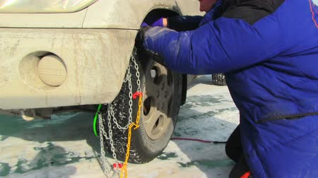 povinnost : Men putting snow chains on tire