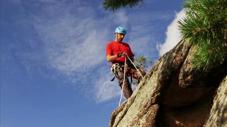 alpinista : Man Descends From The Top Of The Cliff Stock Footage
