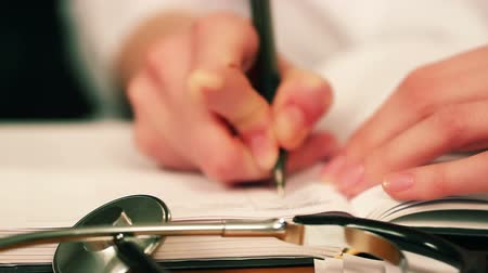 médicos : Doctor writing the note. Focus on stethoscope.