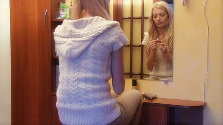 tükör : Beautiful girl looking in the mirror and applying cosmetic