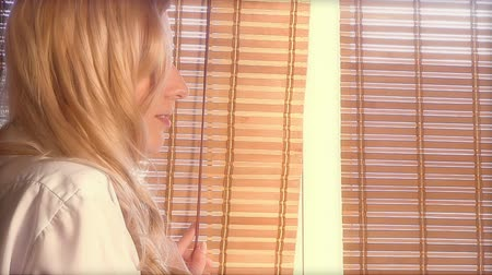 bamboo curtain : Young beautiful woman looking out the window through the bamboo blinds with Sun hotspots on the face Stock Footage