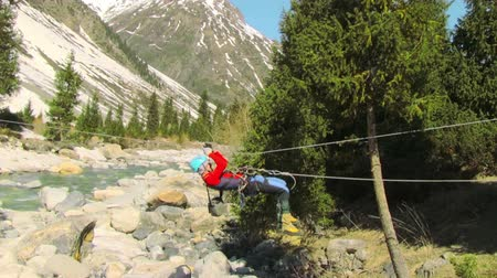 traverse : a man crossing the mountain river by a rope crossing
