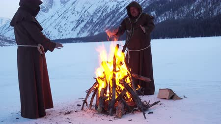 dissenter : monks franciscans are warming near fire in winter Stock Footage