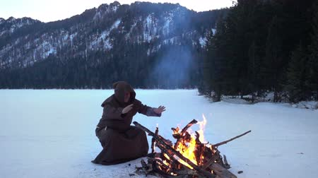 dissenter : Monk franciscans are warming near fire in winter. Slowmotion 240FPS