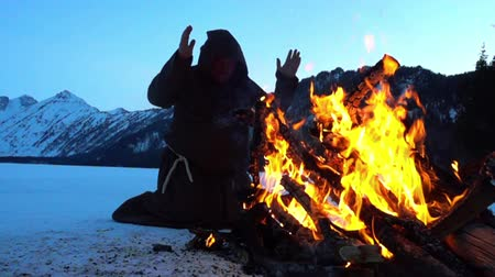 dissenter : Monks franciscans are warming near fire in winter. Slowmotion 240FPS