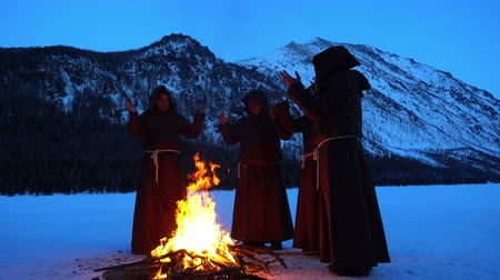 казна : Four monks pray at the campfire in the mountains slow mo