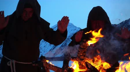 казна : Two monks pray at the campfire in the mountains
