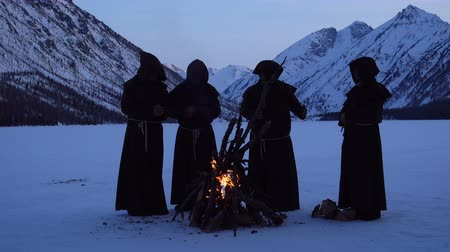 казна : Four monks are warming around  campfire in the winter mountains. 4K UHD