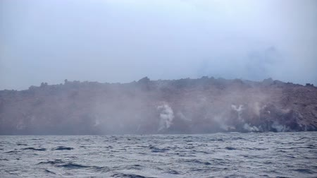 daleko : Okhotsk Sea, Chirpoy Island, Snow volcano activity, Russia. Hot volcanic lava falls into the sea. White fog rises over the shore.