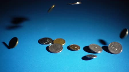 налог : Different coins fall on blue  in slow motion against dark background. 240 FPS