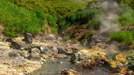 гейзер : Hot drops of water slowly fall in the stream of the geothermal river on the slope of the volcano. Kuril Islands, Itutrup Island, Baranskiy Volcano. Slowmotion 240 FPS