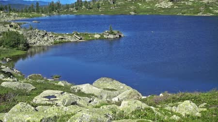 cam : Panorama of a blue mountain lake surrounded by wooded peaks. Western Siberia, Ergaki range.