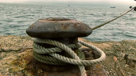 yaşlı : Rusty, old bollard with a rope that fixes a ship in an harbor Stok Video