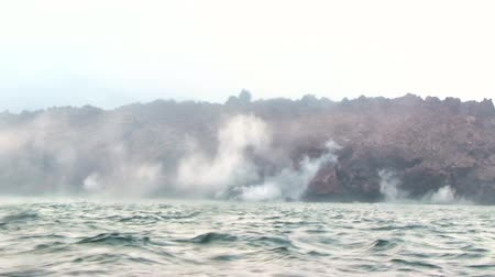 вулканический : Okhotsk Sea, Chirpoy Island, Snow volcano activity, Russia. Hot volcanic lava falls into the sea. White fog rises over the shore.