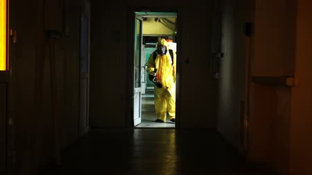 safeness : A man in a yellow protective suit with a black spray goes through a dark corridor