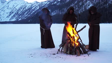 rito : monks franciscans are warming near fire in winter Vídeos