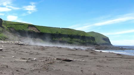 storming : Kuril islads. Onecotan. The steep banks of the island, black volcanic sand, fog rising above the water and old vulkane Nemo. Stock Footage