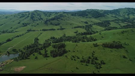 körképszerű : Aerial footage of long road in the green valley between hills Stock mozgókép