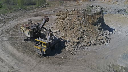 opencast : Aerial view. Excavator loads stones into a dump truck. UHD