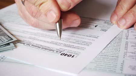refund : Man filling US tax form. tax form us business income office hand fill concept