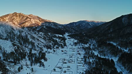 склон : A beautiful aerial shot of winter village, mountain winter resort in Altai Стоковые видеозаписи