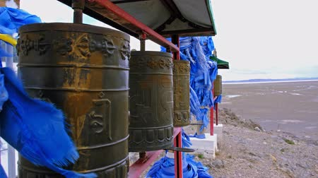 Row of buddhist prayer drums and blue ribbons in west mongolia Wideo