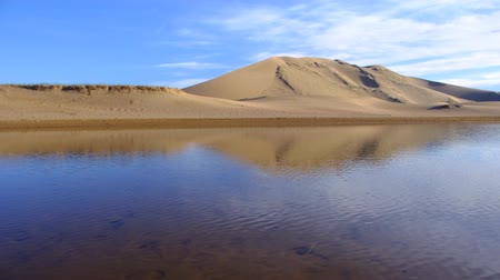 yansıyan : Big sand barkhan reflected in the lake. Mongolia sandy dune desert Mongol Els. Govi-Altay, Mongolia. Stok Video