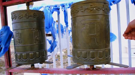 People spins some Buddhist prayer drums. Western Mongolia.