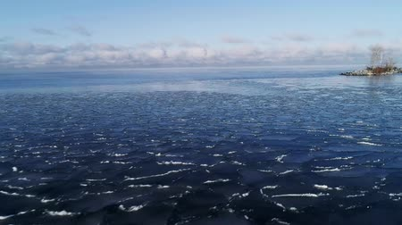 cracked ice floe floating on blue water Stok Video