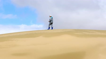 Tourist walking along the edge of the sand dune. Large barkhan in Mongolia sandy dune desert Mongol Els. Govi-Altay, Mongolia.