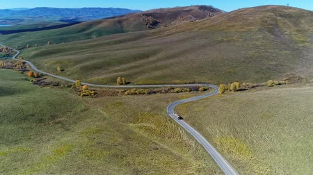 Aerial view of winding road on mountain in autumn hill.