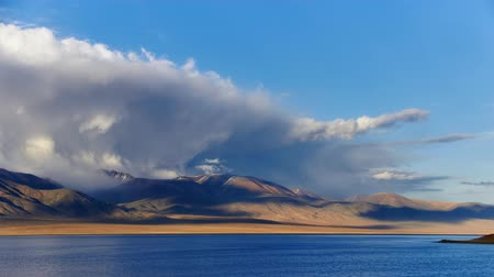 Clouds and shadows moving over evening mountains. Western Mongolia, Tolbo Nuur Lake.