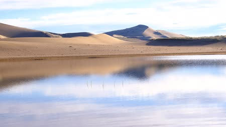 A large lake on the edge of a sandy desert. Mongolia sandy dune desert Mongol Els near lake Durgen Nuur. Khovd province, Western Mongolia.